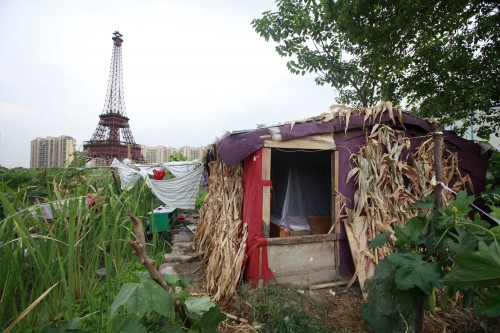 A farmer's house is seen near a replica of the Eiffel Tower at the Tianducheng development in Hangzhou