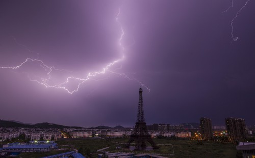 Lightning bolt streaks across the sky above a replica of the Eiffel Tower at the Tianducheng development in Hangzhou